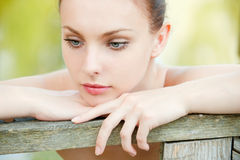 Beautiful woman leans against Royalty Free Stock Images