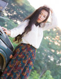 Beautiful woman leans on the car, looking at camera Stock Images