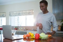 Beautiful woman learning food recipe from laptop. In kitchen Royalty Free Stock Photos