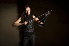 Beautiful woman in leather clothing holding saber Royalty Free Stock Image