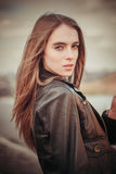 Beautiful woman in leather coat outdoors Stock Photos