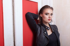 Beautiful woman in leather jacket on red door Royalty Free Stock Image