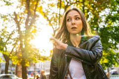 Beautiful woman in leather jacket on the street with sun backlight. Portrait photography with female model outdoor