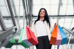 Beautiful woman leaving the mall with plenty of shopping bags Stock Photo