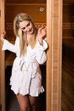 Beautiful woman leaving sauna. Attractive woman wearing a short white bathrobe is posing while leaving the sauna Stock Photo