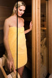 Beautiful woman leaving sauna. Attractive woman wearing a yellow towel is leaving the sauna by a half opened glass door Stock Images