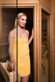 Beautiful woman leaving sauna. Attractive woman wearing a yellow towel is leaving the sauna by a half opened glass door Royalty Free Stock Images