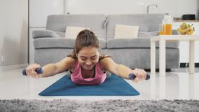 Young woman exercising at home in a living room. A beautiful woman in leggings tries to do exercises on the floor in the living room. Enjoying this process, she stock footage
