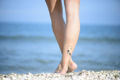 Beautiful woman legs on the beach. Closeup detail of female feet with cat tattoo on a beach stock photo