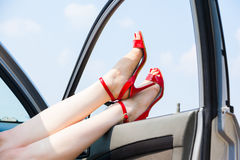 Beautiful woman legs. In red high heels at the car Stock Photo