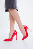 Beautiful woman legs standing in red shoes with high hills Stock Photography