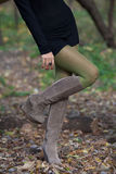 Beautiful woman legs in suede boots in autumn forest Stock Photo