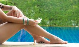 Beautiful woman legs. Sunbathing near swimming pool and hand holding white flower. stock photo