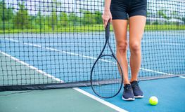 Beautiful woman legs with tennis racket on tennis court. Beautiful female legs with tennis racket on tennis blue court stock photography
