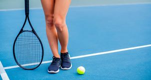 Beautiful woman legs with tennis racket on tennis court. Beautiful female legs with tennis racket on tennis blue court stock image