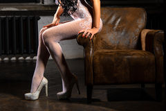 Beautiful woman legs in white stockings on high heels. Sitting on a chair Stock Photo