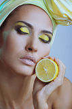 Beautiful woman with lemon in yellow scarf Stock Photography