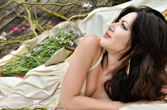 Beautiful woman lie down with flowers outdoor Royalty Free Stock Photography