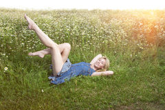 Beautiful woman lies in the field of camomiles Stock Photography