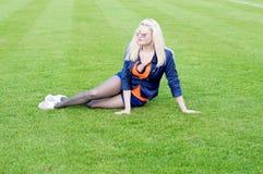 The beautiful woman lies on a football field Stock Photos