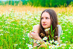 Beautiful woman lies in a green field with flowers Royalty Free Stock Images