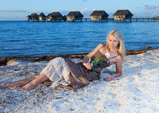 The beautiful woman lies on sand over the sea Stock Photos