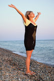 Beautiful woman lifted hands upwards on seacoast Royalty Free Stock Photos