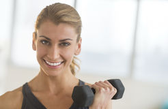 Beautiful Woman Lifting Dumbbell At Health Club Royalty Free Stock Image