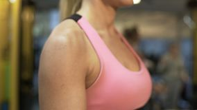 Beautiful woman lifting dumbbells in gym, working out to have perfect body. Stock footage stock footage