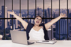 Beautiful woman lifting hands in office Royalty Free Stock Images