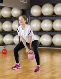 Beautiful Woman Lifting Kettlebell In Health Club Royalty Free Stock Images
