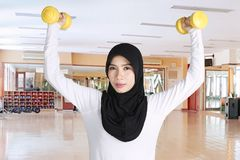 Beautiful woman lifting two dumbbells. Beautiful woman wearing sportswear and veil while lifting two dumbbells in the fitness center Royalty Free Stock Photos