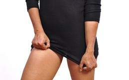 Beautiful woman lifts up short black dress revealing her thighs. Beautiful woman lifts up short black dress and reveals legs on white background Stock Photo