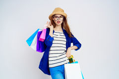 Beautiful woman on a light background holds bags in glasses and in a hat, shopping, shopaholic Royalty Free Stock Photo