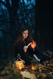 Beautiful woman lighted by candle. Beautiful red hair woman lighted by candle in a forest.Dark fantasy stock image