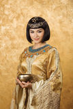 Beautiful woman like Egyptian Queen Cleopatra with cup on golden background Stock Images