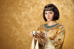 Beautiful woman like Egyptian Queen Cleopatra with cup on golden background Stock Photos