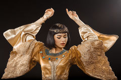 Beautiful woman like Egyptian Queen Cleopatra dancing against black background. Fashion Stylish Beauty Portrait with Black Short Haircut and Professional Make-Up Stock Photos