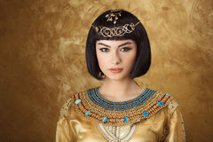 Beautiful woman like Egyptian Queen Cleopatra on golden background. Fashion Stylish Beauty Portrait with Black Short Haircut and Professional Make-Up of stock photo
