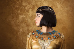 Beautiful woman like Egyptian Queen Cleopatra on golden background. Side view, face profile. Fashion Stylish Beauty Portrait with Black Short Haircut and stock image