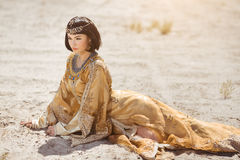 Beautiful woman like Egyptian Queen Cleopatra laying in desert outdoor. Fashion stylish beauty woman with black short haircut and professional make-up of stock photos