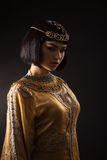 Beautiful woman like Egyptian Queen Cleopatra with serius face on black background. Fashion stylish beauty woman with black short haircut and professional make royalty free stock images