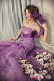 Beautiful woman in a lilac dress. Beautiful woman in a lilac dress with a fan Royalty Free Stock Photos