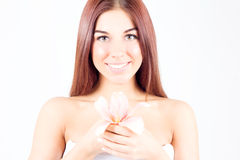 Beautiful woman with lily in hands smiling with teeth. SPA treatment. Stock Photo