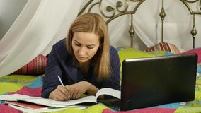 Beautiful woman on-line education in home. Student on a bed with workbook and laptop. slow motion. Beautiful woman on-line education in home. Student on a bed stock video footage