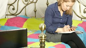 Beautiful woman on-line education in home. Student on a bed with workbook and laptop. 4K. Beautiful woman on-line education in home. Student on a bed with stock video footage