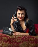 Woman in lingerie with old phone. Beautiful woman in lingerie with black vintage phone Royalty Free Stock Photo