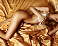 Beautiful woman lingerie model is on a golden silk bed Stock Photography