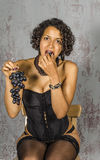 Beautiful woman in lingerie mulatto eat fruit Stock Images