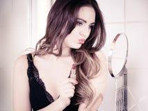 Beautiful woman with lipstick in bathroom. Applying make up concept. Beautiful woman with red lipstick in front of mirror in bathroom. Indoor stock image